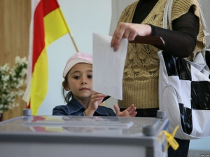 Woman casts ballot in the South Ossetian parliamentary election as her daughter watches (ITAR-TASS)