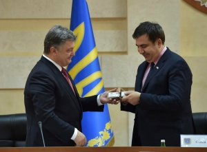 Ukraine's Petro Poroshenko hands Mikheil Saakashvili his identification card, identifying him as the new governor of the Odessa Oblast. (Press office photo)